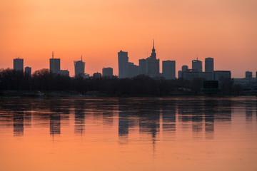 Obraz Panorama wieżowców w Warszawie podczas kolorowego zachodu słońca, odbicie w Wiśle, Polska - fototapety do salonu