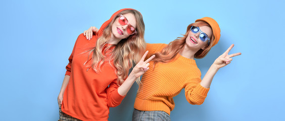 Two Lovable embracing fashionable woman sisters dance in Trendy orange outfit. Studio shot of Carefree funny stylish friends laughing on blue. Happy fashion girl, dancing positive mood, peace sign Wall mural