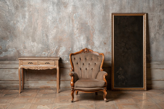 An old chair, a mirror and a table on background of vintage wall