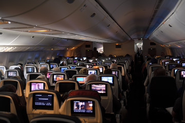 Interior of a jet airplane on a long international flight with TV screens on the back of seats
