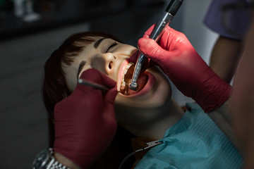 Senior male dentist drilling tooth to young female patient in dental chair Wall mural