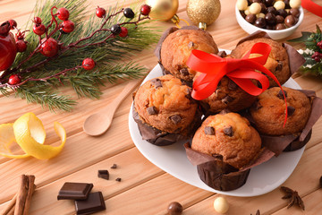 Plate with muffins on table with Christmas decoration elevated view