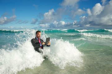 Overwhelmed young businessman in a full suit having a rough time using his tablet computer to surf the web in crashing waves on the shore of a tropical beach