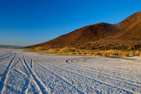 tire tracks on blinding white salt flats in Mojave desert near Zzyzx road with hill in the background