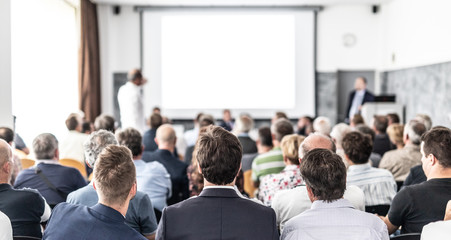 I have a question. Group of business people sitting at the chairs in conference hall. Businessman standing up asking a question. Conference and Presentation. Business and Entrepreneurship. Wall mural