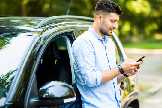 Handsome young man standing and using the phone with his car.