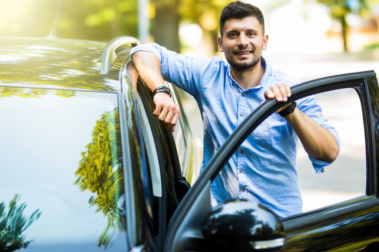 Handsome young man standing on the road near opened door of his car.