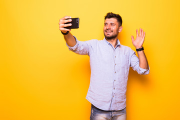 Young man in casual outfit taking a picture of himself, using smart phone, having video call with friends, sending greetings with palm over yellow background