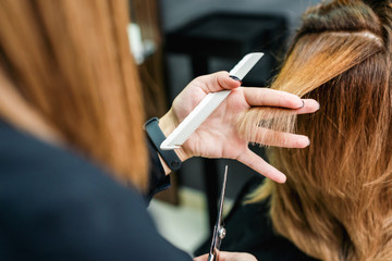 Female hairdresser is holding in hand between fingers a red hair is cutting woman hair close up.