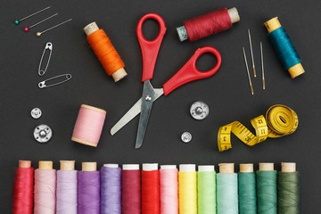 Colored thread coils, scissors, buttons, needles, pin and a tailor meter on a black background. The...