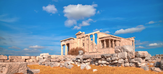 Fototapete - Panoramic image of Erechtheion temple Acropolis, Athens, Greece, with famous Caryatides in Autumn with orange grass and blue sky with clouds