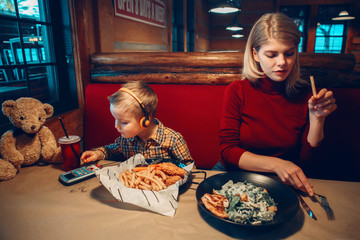 Caucasian family mother with toddler boy son eating food dinner in cafe restaurant and playing electronic digital gadget device toy. Children kids addiction to cell mobile phones.