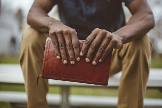 Closeup of a male sitting in the park while holding the bible
