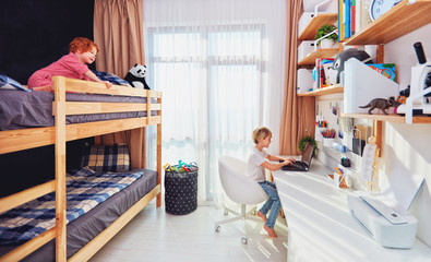 two boys, brothers in kids room with bunk bed and wall shelves