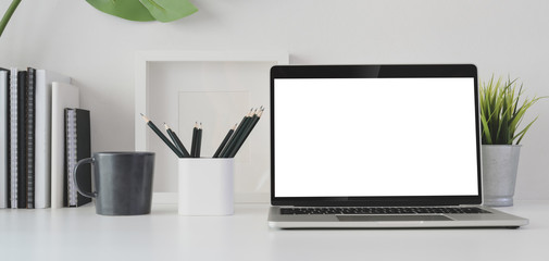 Cropped shot of modern office room with blank screen laptop computer and office supplies
