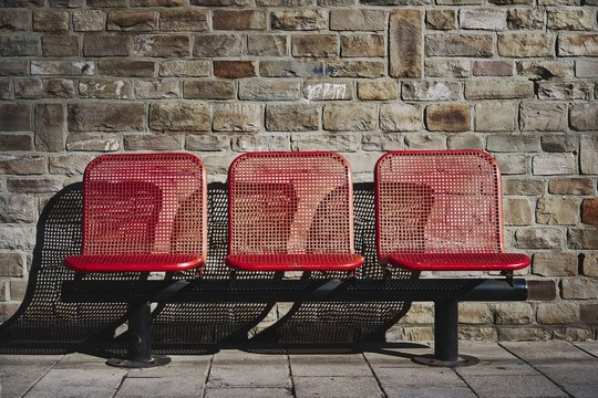 Beautiful shot of three red seats in the bus station of an urban area