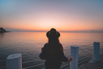 One lonely carefree traveler woman in a hat on a sea pier at sunset. Happy concept, free people and enjoying life