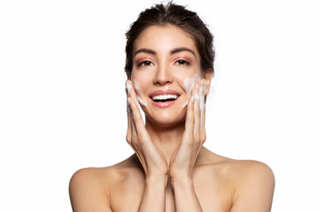 Happy smiling young woman cleaning face with soap foam studio portrait. Pretty girl massaging skin on cheeks. Face skincare natural cosmetic. Morning routine, facial beauty treatment. White copy space