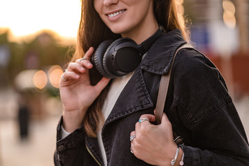 Stylish casual fashionable hipster student woman teenager with black wireless headphones while walking around the city. Lover music enjoys listening music