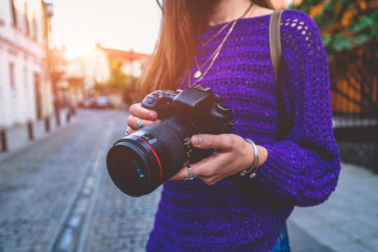 Stylish casual traveler photographer woman taking pictures with digital dslr camera and slr lens during walking around european city