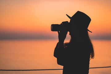 Silhouette of a woman photographer in hat with dslr camera during taking photos at sunset