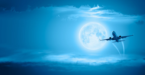 """Passenger airplane in the sky against full moon """"Elements of this image furnished by NASA """""""