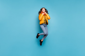 Full body photo of beautiful lady jumping high enjoy weekend playful mood warm weather wear stylish windbreaker jeans scarf sweater isolated blue color background