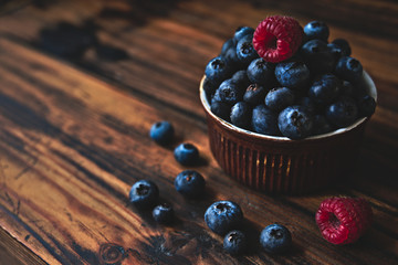 Closeup of fresh blueberries and raspberries on rustic wooden table