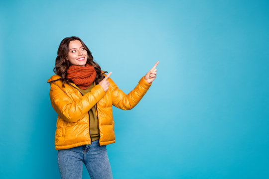 Photo of pretty cute lady indicating fingers empty space showing best shopping prices wear stylish autumn windbreaker jeans scarf pullover isolated blue color background