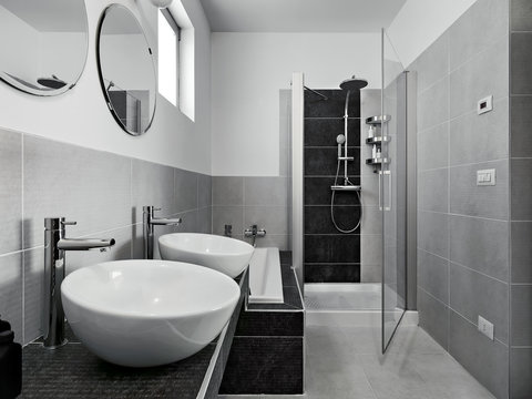 interior view of a modern bathroom in foreground two countertop washbasin on the background the masonry shower box with glass door