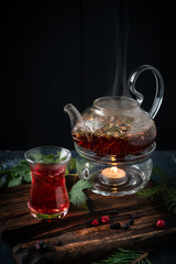 A glass of herbal tea with blackcurrants in a teapot on a dark wooden background. Fragrant natural drink from wild berries.