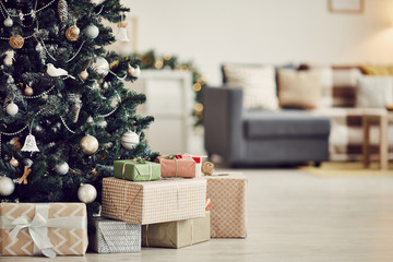 Image of decorated Christmas tree with gift boxes under it on the floor in the living room