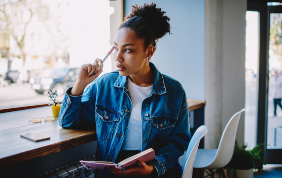 Thoughtful female blogger looking away and feeling pondering on ideas for new article at own web page, pensive woman sitting in cafeteria with textbook in hand and thinking about plan for future trip