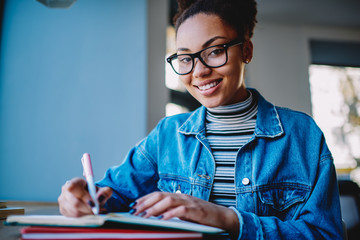 Portrait of cheerful hipster girl in spectacles for provide eyes protection looking at camera during planning week with notebook, successful female student working on ideas for school project