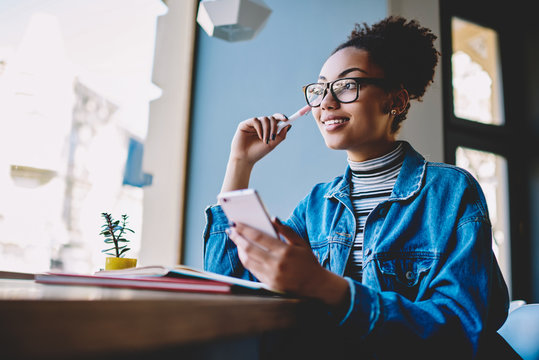 Positive contemplative hipster girl in stylish eyewear for vision correction looking away and thinking on idea for content to web page during break from exam preparation with knowledge textbook
