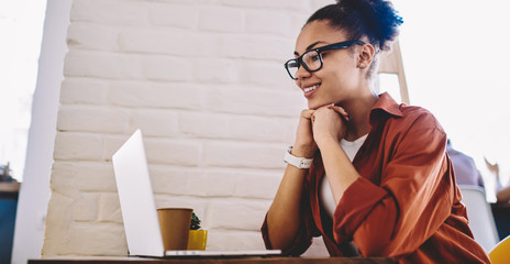 Happy black woman in optical eyewear for vision correction reading information in profile of famous blogger in social networks, cheerful hipster girl watching positive movie on content website