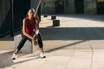 Calm attractive sportswoman sitting alone outdoors stock photo