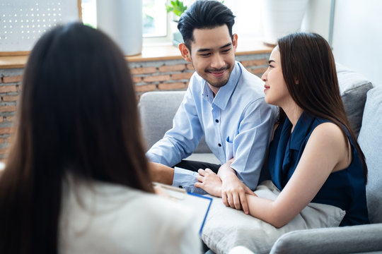 Asian couple patients sitting on sofa explaining and consulting problem to professional psychologist female, feeling happy after get some advice and can solve problem. Psychology consultant concept.