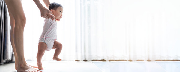 Asian baby taking first steps walk forward on the mat. Happy little baby learning to walk with mother help at home. Mother teaching how to walk gently. Baby growth and development concept. Banner size