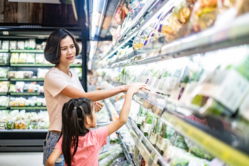 Young Asian beautiful mother holding grocery basket with her child walking in supermarket. She is choosing green salad vegetable picking up from shelf with her little daughter. Shopping for healthy.