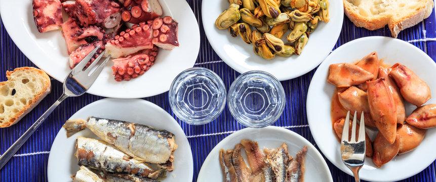 Raki, ouzo glasses and seafood appetizers background, closeup view