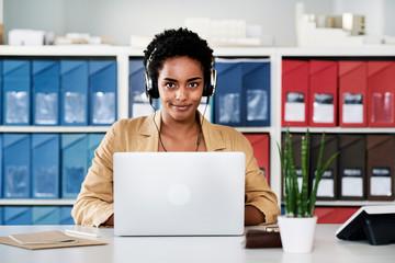 Entrepreneur in headphones using laptop.