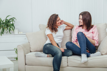 Two attractive girlfriends sitting on the sofa, talking excitedly, smiling.