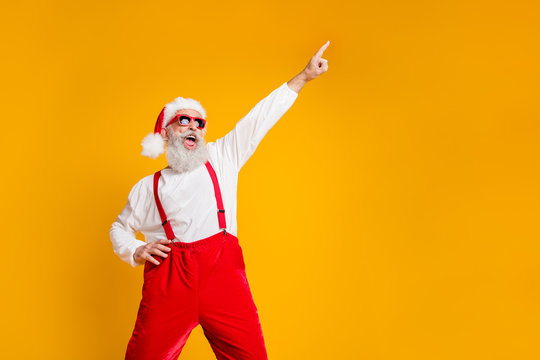 Portrait of funny crazy santa claus hipster in red hat fun christmas x-mas party celebrate newyear time dance raise index finger wear shirt suspenders isolated yellow color background