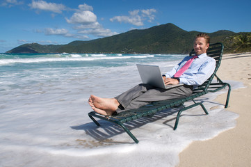 Businessman typing on his laptop on a beach chair working remotely from the shore of an empty tropical beach