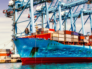 Container ship in the port loading and unloading containers