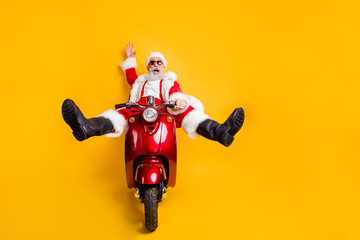 Full size photo of amazed funny crazy santa claus in red hat drive fast scooter want hurry on x-mas christmas party shirt suspenders isolated over yellow color background