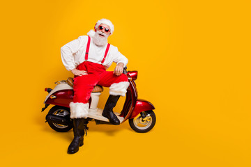 Full size photo of funny santa aged man in festive mood ready for x-mas theme party sitting on vintage bike wear sun specs pants cap shirt boots isolated yellow color background