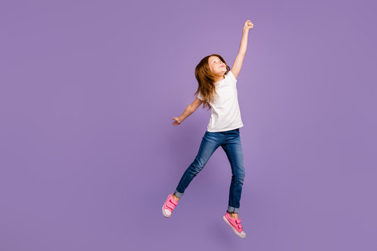 Full body profile photo of funny small ginger lady jumping high rejoicing in air imagine umbrella flight wear casual t-shirt jeans isolated purple background
