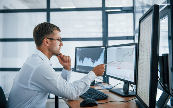 Analysing graphs. Young businessman in formal clothes is in office with multiple screens. Conception of exchange and money
